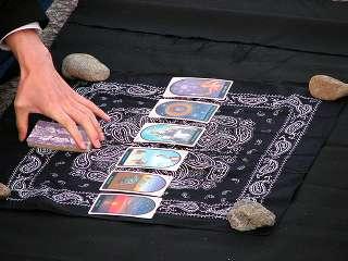 immagine raffigurante 8 carte allineate orizzontalmente e stese su di un panno nero tenuto fermo con 4 pietre