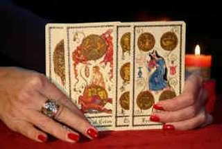 immagine raffigurante 4 carte da briscola tenute in mano da una cartomante ed appoggiate su di un panno rosso