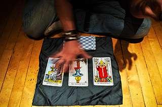 foto sfocata con cartomante inginocchiato che passa una mano sulle carte