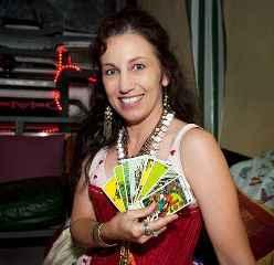 immagine di una cartomante sorridente mentre tiene in mano a ventaglio 8 carte dei tarocchi