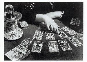 immagine in bianco e nero con la cartomante che indica una carta