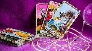 immagine raffigurante il mazzo dei tarocchi con 3 carte in primo piano su di un panno colore fucsia