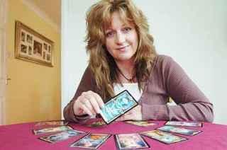 immagine raffiguranate una cartomante che tiene in mano una carta e con i tarocchi stesi a semicerchio sul tavolo