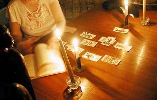 immagine raffigurante una cartomante che sfoglia un libro su un tavolo su cui sono stesi a croce alcuni tarocchi