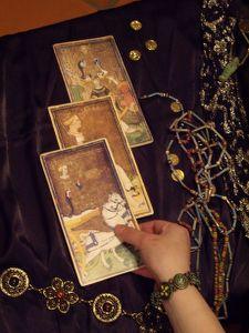 cartomante che tiene in mano una carta dei tarocchi