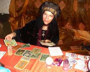 immagine raffigurante una cartomante con un cappello che sorride mentre dispone i tarocchi sul tavolo